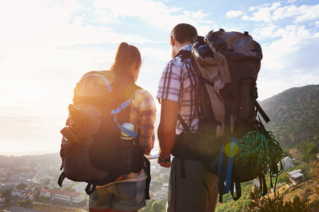 adventure holiday: Rearview of couple with backpacks on standing on a hiking trail looking at the view