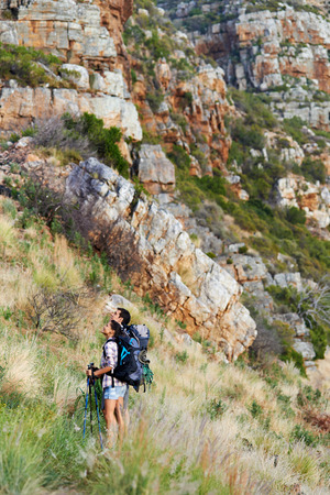 Hiking couple looking up at alrge mountain range photo