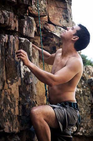manly man: An attractive man with no shirt on rock climbing
