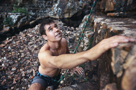 recreational climbing: A handsome man with no shirt on rock climbing with copyspace
