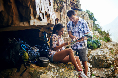 A couple taking a break from their hiking trail and looking at a map photo
