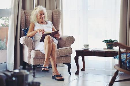 彼女のラウンジで彼女の本を楽しんでいる老婦人
