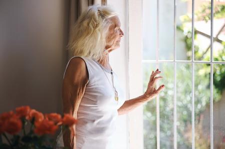 Eine ältere Frau schaut aus ihrem Fenster auf etwas zu warten Standard-Bild