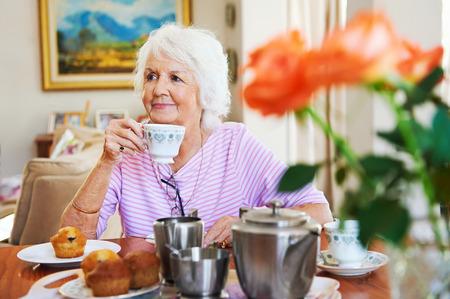 紅茶とマフィンを楽しんでいるコンテンツの老婦人