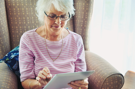 pensions: A mature woman concentrating on a digital tablet Stock Photo