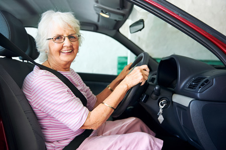 manejando: Retrato de una mujer sonriente envejecimiento sentado en un vehículo Foto de archivo