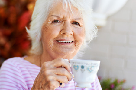 mature women only: Portrait of a smiling older woman having a cup of tea