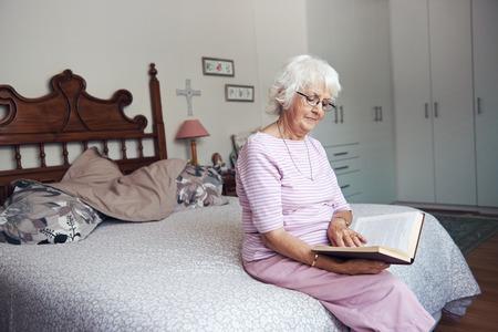 늙은 여자가 copyspace 책을 읽고 그녀의 침대에 앉아 스톡 콘텐츠