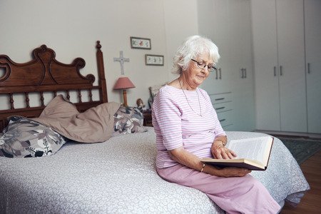 An old woman sitting on her bed reading a book with copyspace