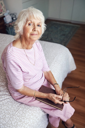Portrait of a senior woman sitting on her bed with her book in her lap photo