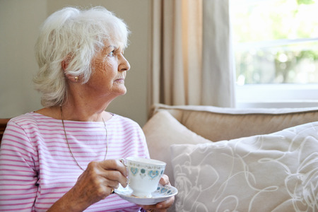 A mature woman  holding a cup and saucer while looking out the window with copyspace photo