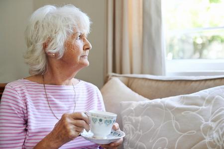 Zralá žena drží šálek s podšálkem při pohledu z okna s copyspace Reklamní fotografie