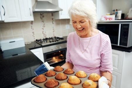 単にオーブンから焼かれたマフィンのトレイを持って笑う祖母