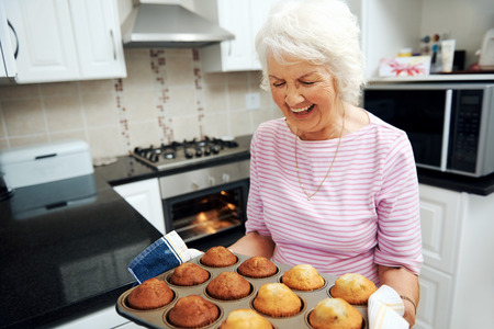 baking tray: A laughing grandmother holding a tray of baked muffins just out of the oven