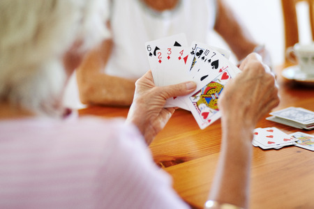 Close up shot of two elderly friends playing a card game 版權商用圖片