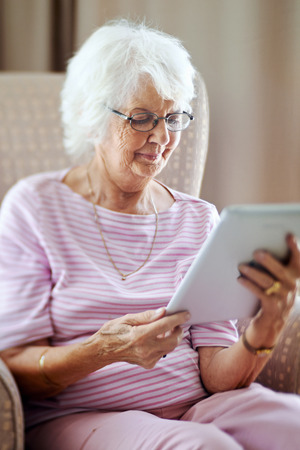 Mature woman looking at her digital tablet photo