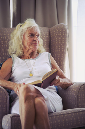 old sofa: A senior woman holding a novel while sitting on her couch
