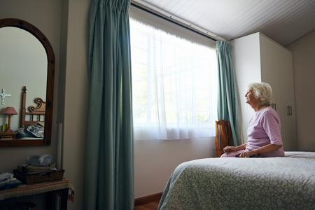 窓の外を見て彼女のベッドの上に座って意気消沈した高齢者の未亡人