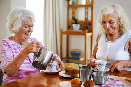 women friends: Two elderly women having tea and muffins together