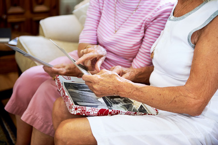 old photograph: Cropped shot of elderly women feeling nostalgic and looking at old photographs
