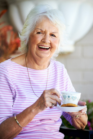 one mature woman only: Grandmother laughing and positive having some tea