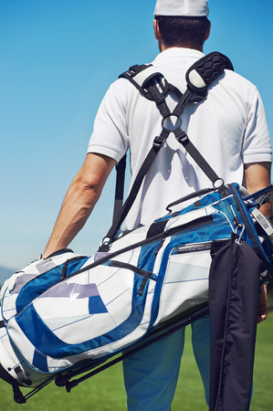 golfing: Golf player walking and carrying bag on course during summer game golfing