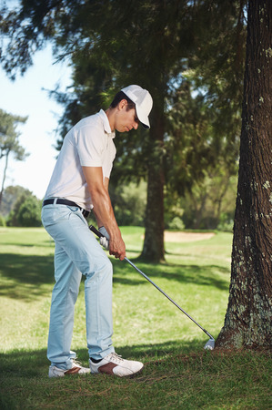 unfavorable: golfer in difficult situation behind tree in the rough a result of poor shot