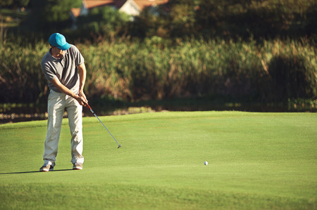 Golf man putting on green and aiming to sink golf putt shot on course Stock Photo - 28176179