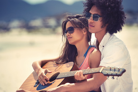 serenading: Cute hispanic couple playing guitar serenading on beach in love and embrace