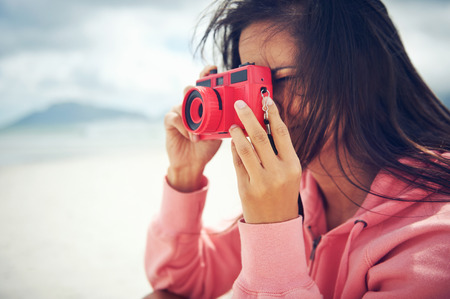 Woman taking photo with old lomography lomo film camera hipster style