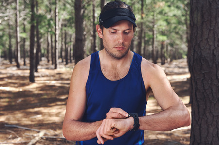 Man looking at stopwatch to check gps pace and time on trail run photo