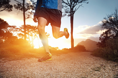 trail runner man exercising for fitness at sunrise in mountains doing sport photo