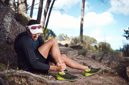shin: running injury for trail runner on mountain twisted ankle Stock Photo