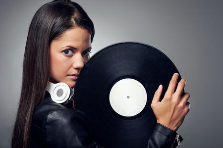 Woman dj portrait with vinyl record and headphones photo