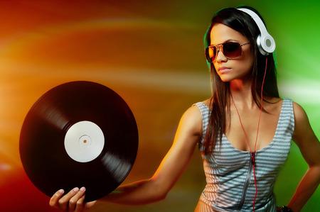 Woman dj portrait with vinyl record and headphones Stock Photo