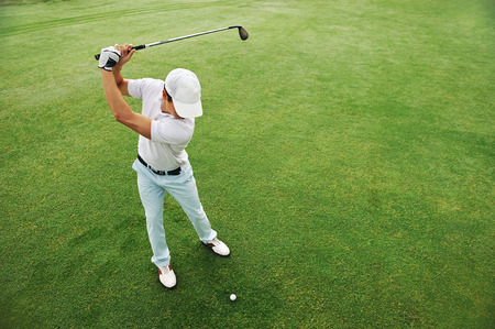 Hög overhead vinkel tanke på golfare slår golfboll på fairway grönt gräs
