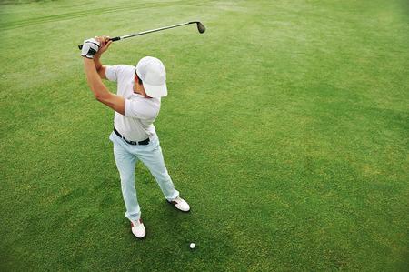 Hoge overhead hoek bekijken van golfer raken golfbal op fairway groene gras