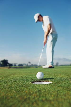 Golf muž uvedení na green pro birdie, zatímco na dovolené