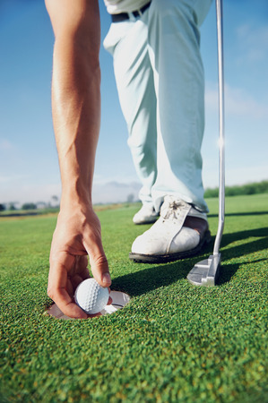 Golf man putting on green for birdie while on vacation Stock Photo