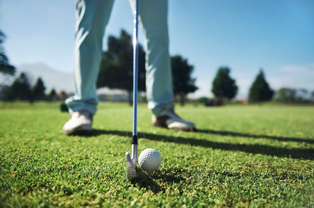 Closeup of golfer with iron hitting tee shot Stock Photo