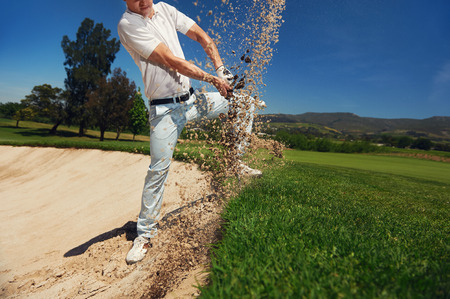 trap: golf shot from sand bunker golfer hitting ball from hazard