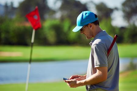 グリーンの横に携帯電話の gps デバイスにスコアを取ってのスマート フォンを持つ近代的なゴルフ男