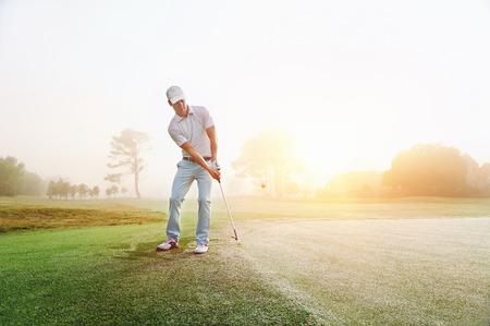 Golfista štěpkování na green při východu slunce na golfovém hřišti v mlžných podmínkách