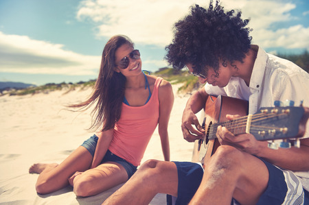 girl playing guitar: Cute hispanic couple playing guitar serenading on beach in love and embrace