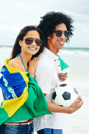 Portrait of latino couple with Brasil flag and soccer ball for world cup photo