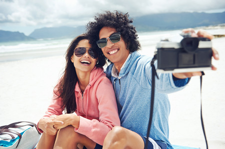 couple taking selfie self portrait at the beach with retro hipster camera photo