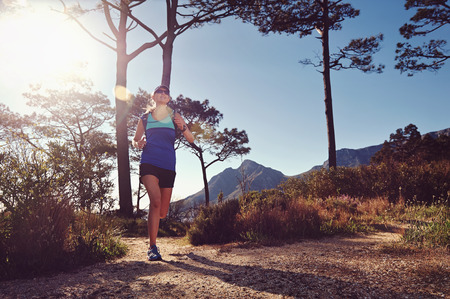Fitness woman trail running in the mountains at sunrise helathy lifestyle photo