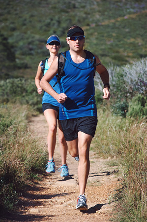 Fit marathon couple trail running together for sport and healthy living photo