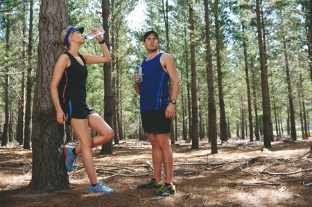 Couple take rest to drink water after running marathon on trail photo