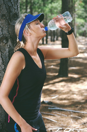 quench: trail runner resting and drinking water for refreshment after marathon